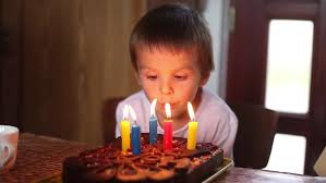 cute little blowing out candles on birthday cake and