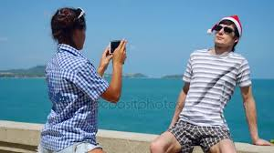 Happy couple wear Santas Hat taking photo with smartphone on the
