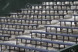 blue benches on a grey concrete ground in rows stadium seats