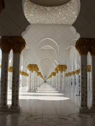 a hallway the columns are decorated with ornaments in gold