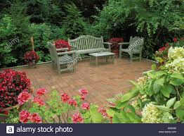 elegant private brick patio with blooming shrubs and flowers