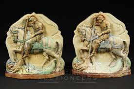 a pair of compton pottery bookends in the form of st george and