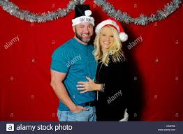 cute couple in a holiday photo booth wearing santa hats and