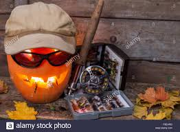 halloween pumpkin background halloween pumpkin head in hat with fly fishing tackles on wooden