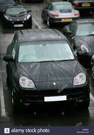 porsche cayenne black porsche cayenne black parked in rainy garage forecourt stock photo