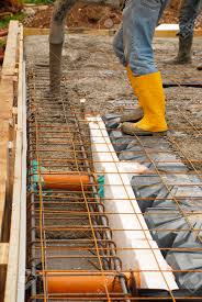 small house builders builders pour concrete onto the foundations of a small house