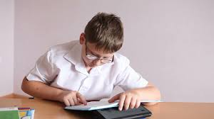 Picture Of Student Sitting At Desk by Boy Student Reading A Paragraph In The Textbook Sitting At A