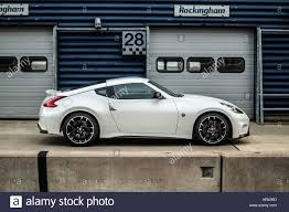 white nissan car side profile of a white nissan 370z nismo on a race track in pit