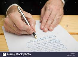 pen writing on paper a businessman writing with a fountain pen on a white paper set on a businessman writing with a fountain pen on a white paper set on a wooded deck