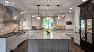 large transitional kitchen design has two islands and a mix of