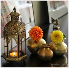 Diwali Decorations At Home by Antique Brass Kundas With Single Stems Of Dahlias Tucked Into Them