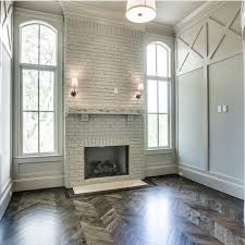 brick fireplace and herringbone flooring a stylish home is a