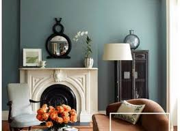 earth tone living room with green wall paint and gray sofa for