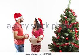 young couple is dancing close to christmas tree woman is pregnant