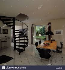 black spiral staircase in modern white hall dining room with white