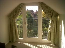 green fabric Window Curtains on the hook connected by glass windows