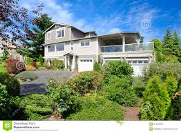 large grey house with many windows and three car garage house w