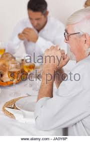 family praying before thanksgiving dinner stock photo royalty