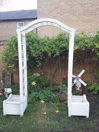 white keter garden arch archway with two planters and trellis in
