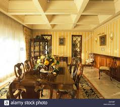dark wooden table and chairs in spanish dining room with yellow