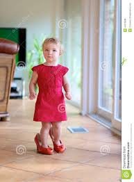 funny toddler walks at home in mama u0027s shoes stock photo
