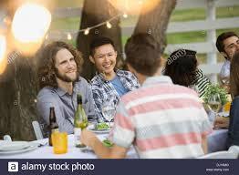 multiethnic friends enjoying outdoor dinner party stock photo