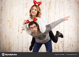 couple in fake deer horns posing have fun over wooden background