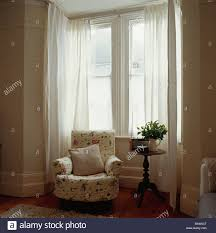 patterned cream armchair in front of bay window with white voile