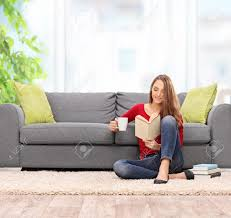 young woman reading a book and drinking coffee seated on the