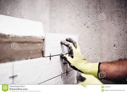 worker placing small ceramic tiles with plastic spacer on bathroom
