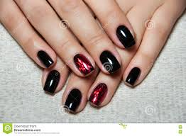 black nails with red foil on the ring finger stock photo image