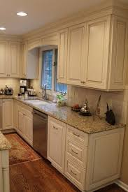 antique white kitchen cabinets with subway tile backsplash white kitchen cabinets with a glaze granite counters and