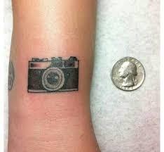small simple camera tattoo on arm tattoomagz
