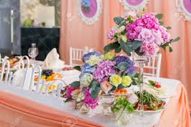 wedding flowers ta table set for wedding banquet with floral composition of roses