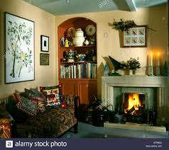 bookshelves in alcove beside tiled fifties fireplace in nineties