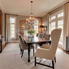 traditional crystal chandelier with elegant tufted chairs for