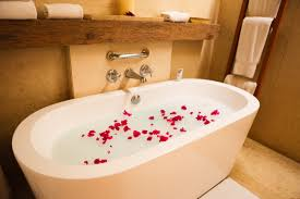 bathroom outdoor bathtub on wooden deck matched by flower