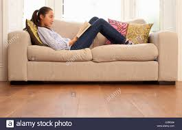 teen reading a book with feet up on the table uk stock photo
