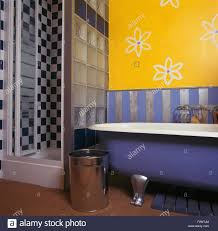 stylised flowers drawn on wall above roll top bath in bright