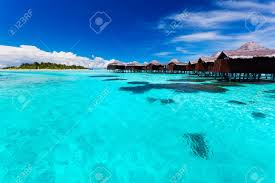 overwater bungallows in blue lagoon around tropical island in