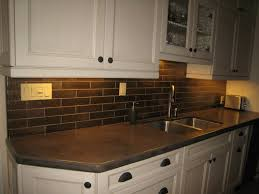 dark grey subway tile backsplash and white farmhouse kitchen sink