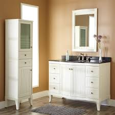 dark countertop white bathroom cabinets under framed round mirror
