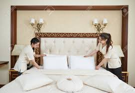bed making hotel service female housekeeping worker maid making bed with