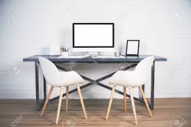 Designer Desk by Two Chairs Next To Designer Desk With Blank White Computer Screen