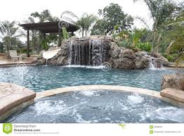 a pool with a waterfall in a luxury backyard stock photo image