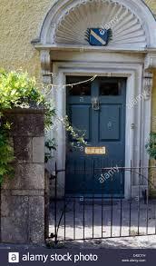 metal gate in front of georgian house with blue front door below