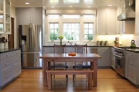 two tone kitchen cabinets with black countertops the table in the center and two tone cabinets