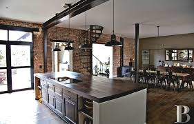 endearing industrial kitchen with brick walls and dark wood