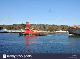 red tugboat pulling double hull fuel oil barge through cape cod