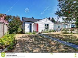 small white rambler house with red front door stock photo image
